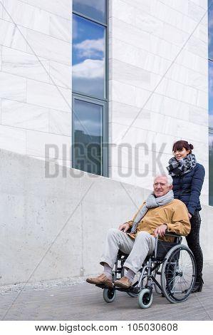 Senior Assistant Pushing A Wheelchair