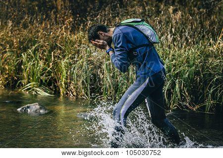 male athlete running across river