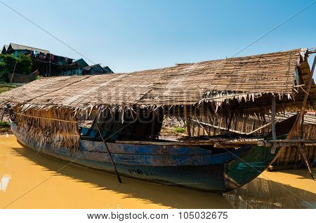 Wooden boat on muddy river