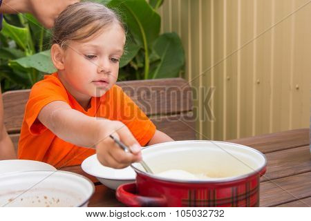 Girl Scoop Ladle Porridge From The Pot