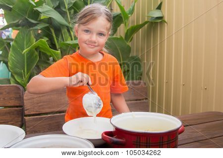 Happy Little Girl Puts Cereal In A Bowl