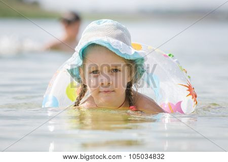 Concentrated Four-year Girl With A Circle Floating In The River