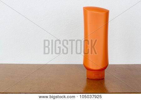 Orange Bottles Of Health And Beauty Products Cosmetic On The Wood
