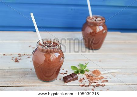 chocolate and banana smoothie with chocolate balls in jars on white rustic table top view