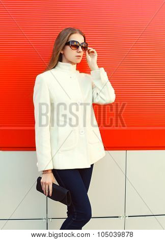 Fashion Elegant Woman Wearing A White Coat Jacket With Clutch Bag Over Red Background