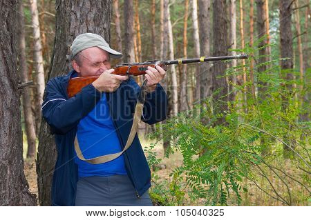 Hunter in forest aim a rifle