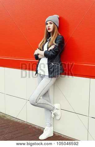 Fashion Stylish Pretty Woman Wearing A Rock Black Leather Jacket And Hat Over Red Background