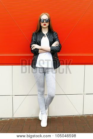 Fashion Stylish Pretty Woman Wearing A Rock Black Leather Jacket And Sunglasses In City Over Red Wal