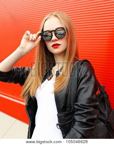 Portrait Fashion Pretty Woman Wearing A Rock Black Leather Jacket, Sunglasses And Bag Over Red Backg