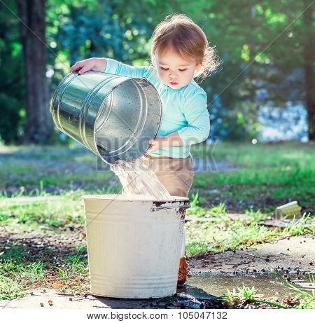 Toddler Girl Playing Outside With Buckets