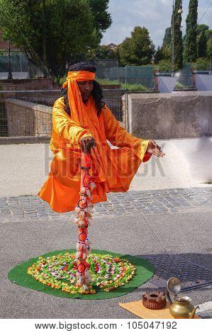 Magician yogi meditates in bright orange robes