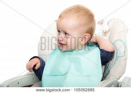 The Small Child In A Bib And A Children's Stool Looks Aside