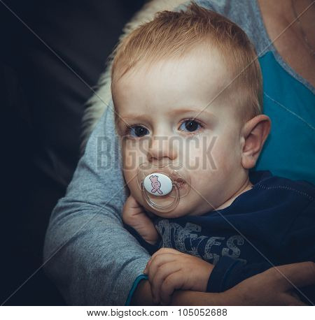 The Hand Of The Woman Presses To Itself The Small Unfortunate Scared Child In A Pacifier In A Mouth