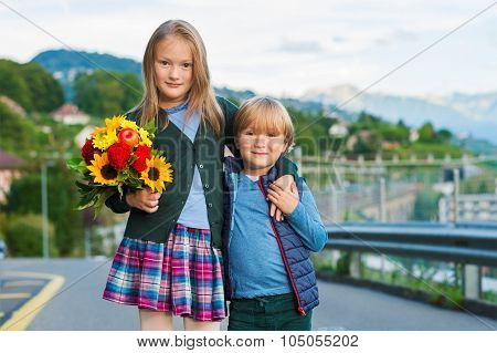 Outdoor portrait of a cute little kids with beautiful bouquet of flowers