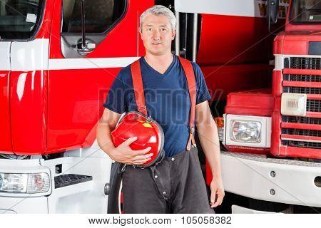 Portrait of confident mature fireman holding red helmet against firetrucks at station