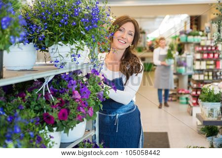 Portrait of smiling mid adult florist pushing flower shelves in shop