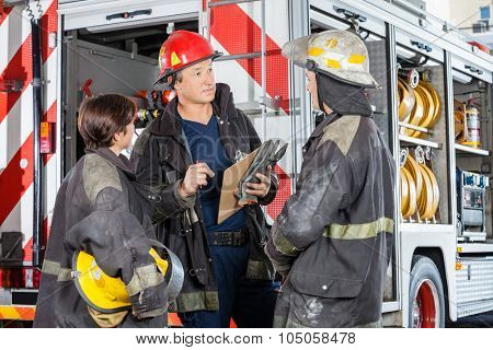 Male and female firefighters discussing while standing against truck at fire station
