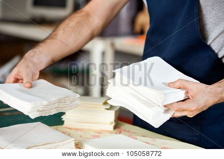 Midsection of male worker stacking papers at table in factory