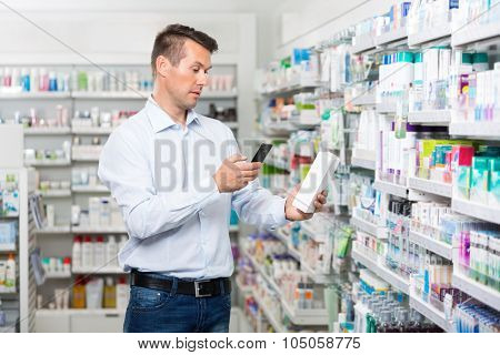 Mid adult male customer scanning product through mobile phone in pharmacy
