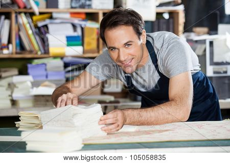 Portrait of mid adult male worker analyzing papers at workbench in factory