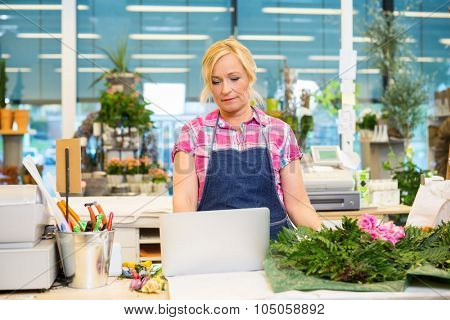 Mature female florist using laptop at counter in flower shop