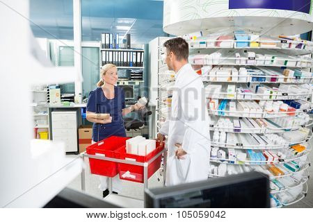 Male pharmacist and female assistant counting stock in pharmacy