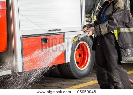 Midsection of firewoman spraying water during training at fire station