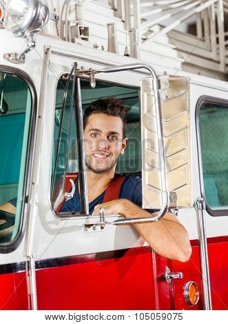 Portrait of smiling young male firefighter sitting in firetruck