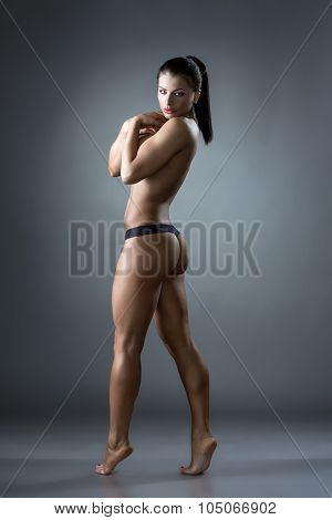 Seminude female bodybuilder posing at camera