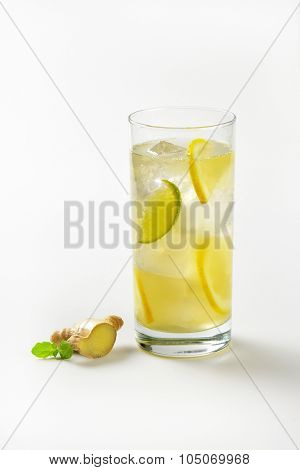 glass of ginger ice tea with lemon and fresh ginger on white background