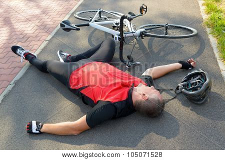Bicycle accident. Biker lying on the road