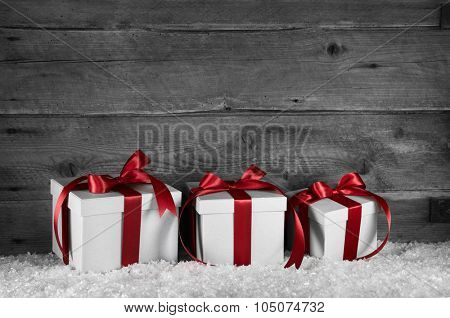 Three red white christmas presents on old wooden grey background for decoration.