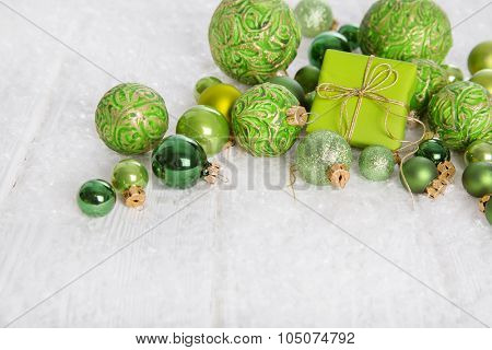 Green and white christmas background with gift box, snow and balls for decoration items.