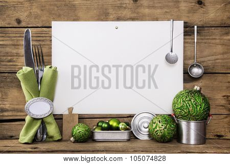 White sign on old wooden background decorated with silver cutlery, dishes and green christmas balls for a menu card.