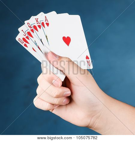A royal straight flush playing cards poker in hand in hearts