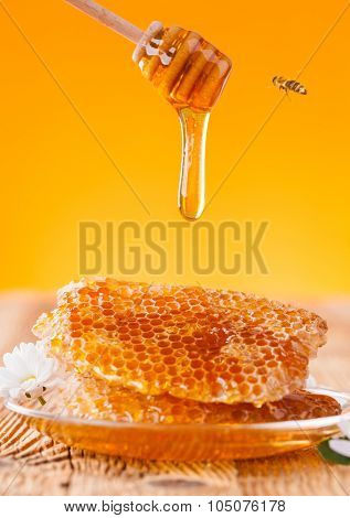 Fresh honey jar with dipper, served on wooden planks
