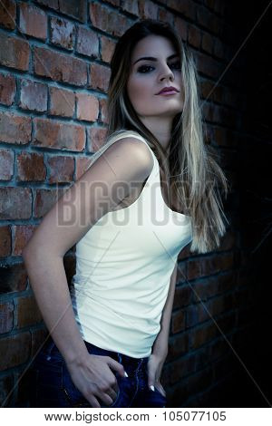 Young girl posing next to a brick wall