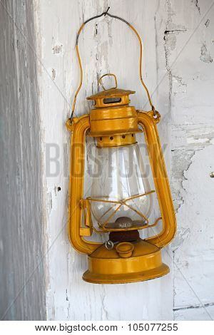 Old dusty oil lamp on wooden wall