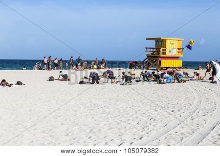 People Do Fitness Training At The Beach Next To A Lifeguard Tower