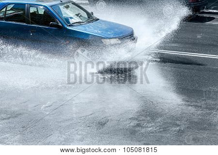Car Splashes Through Large Puddle On Wet Road