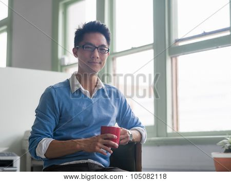 Portrait of young successful businessman in office