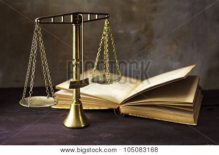 Vintage Brass Scales Of Justice And An Old Book On A Brown Wooden Table