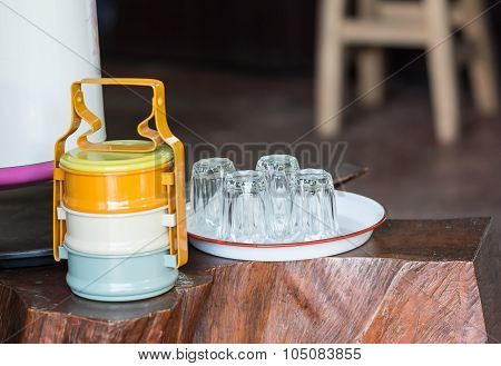 Four Empty Clear Glass Put Upside-down On Tray With Colorful Food Carrier On Wooden Table In Vintage