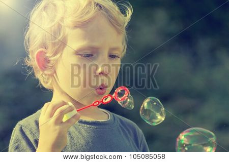 Little Blond Boy With Soapy Bubbles Outdoors
