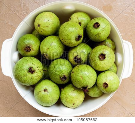 Mix of ripe and unripe freshly plucked Guava kept on a bowl on a plain background