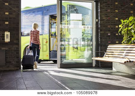 Female traveler going on the bus at terminal