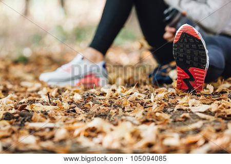 runner woman rest on the leaves in park