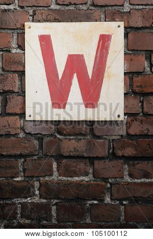 Old sign with letter W on a brick wall.