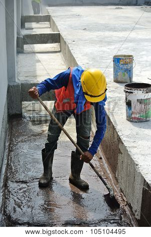 A construction worker apply layer of waterproofing at the building roof slab surface