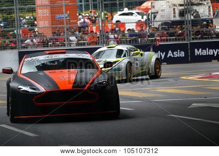 KUALA LUMPUR, MALAYSIA - AUGUST 08, 2015: Gerard Yap drives a Vantage N24 GT4 car (orange/black) takes turn 2 at the inaugural 2015 Kuala Lumpur City Grand Prix.